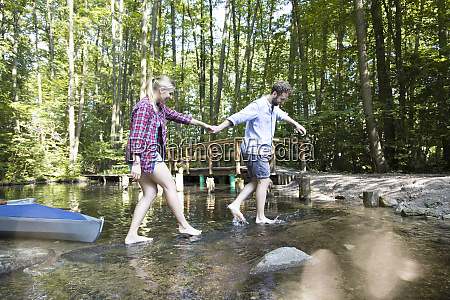 young couple crossing a forest brook