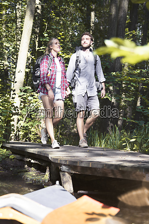 young couple crossing a bridge in