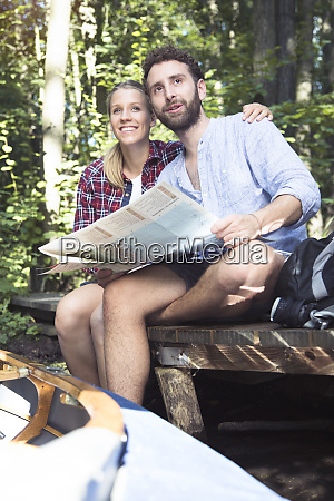 young couple with map and canoe
