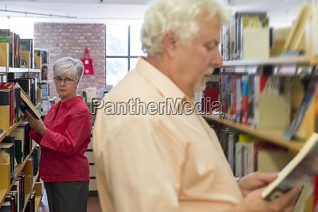 senior woman watching man reading book