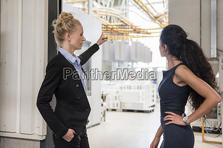 two women talking in modern factory
