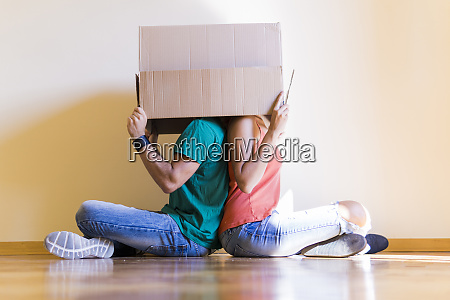 couple with heads in cardboard box