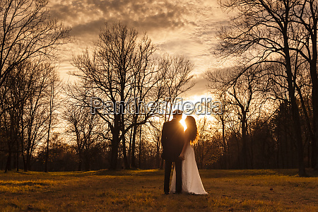 happy bridal couple embracing in park