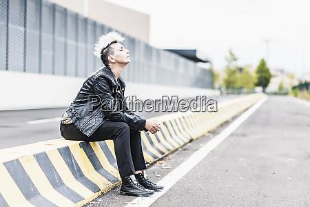 punk woman sitting at the roadside