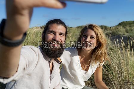 happy couple taking smartphone selfie in