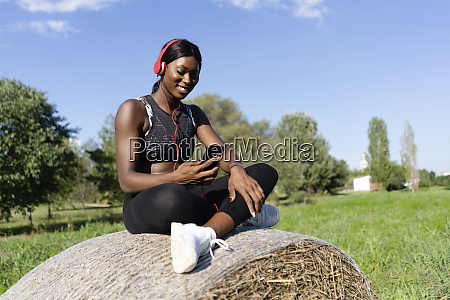 young athlete sitting on straw bale