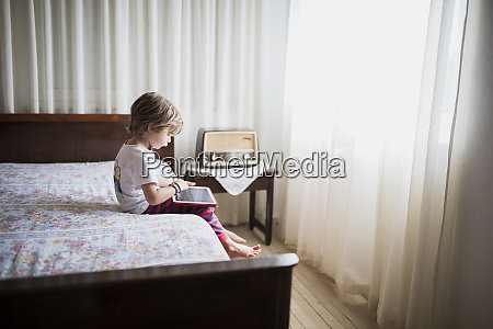 young boy sitting on bed using