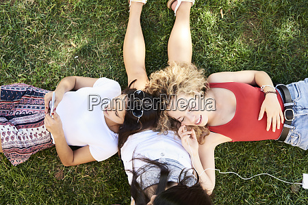three young women lying in grass