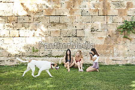 three young women sitting at stone
