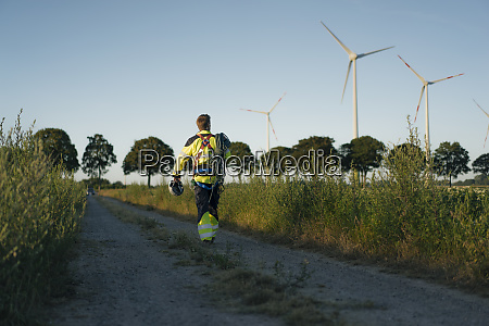 technician walking on field path at