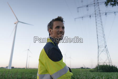 smiling engineer next to a wind