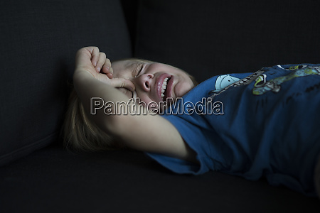 crying boy lying on couch