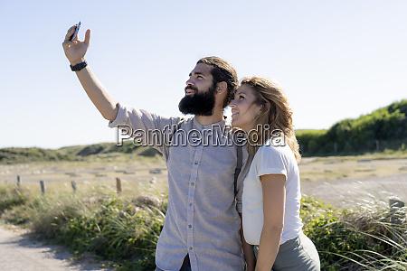 young couple taking smartphone selfies on