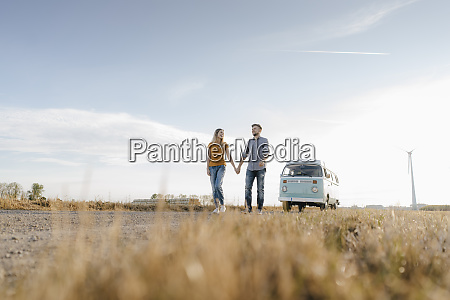 young couple walking on dirt track