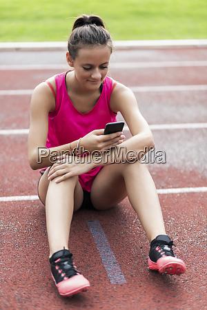 teenage girl sitting on race track