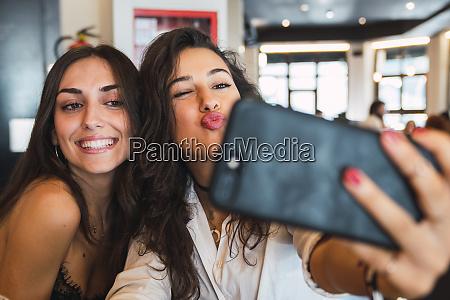 portrait of two friends taking selfie
