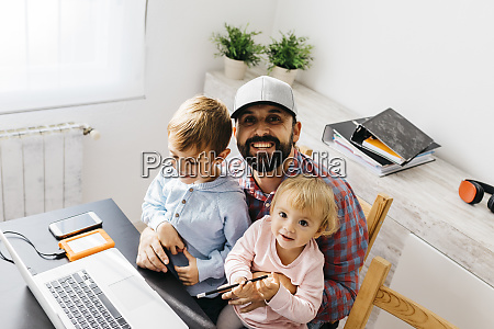 father working at home using laptop