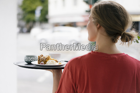 rear viewof young woman serving coffee