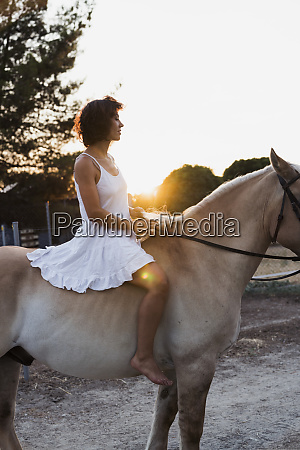 barefoot woman riding bareback on horse
