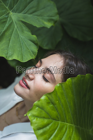 young woman under green leaves with
