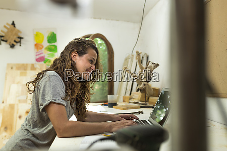 craftswoman using laptop at her desk