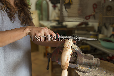 craftswoman filing a piece of wood