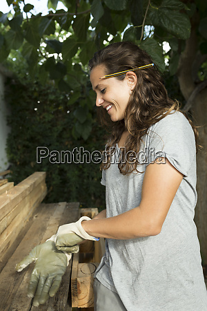 smiling craftswoman putting on protective gloves