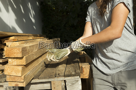 craftswoman putting on protective gloves at