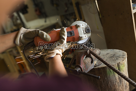craftswoman using angle grinder in her