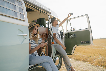 young couple with cell phones relaxing
