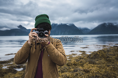 young man with woolly hat taking