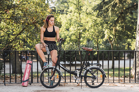 fit young woman with bicycle leaning
