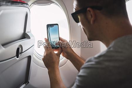 man in airplane using smartphone taking