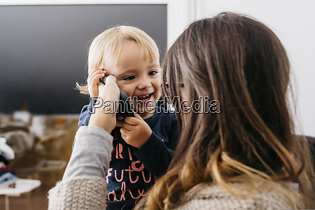 mother giving cell phone to happy