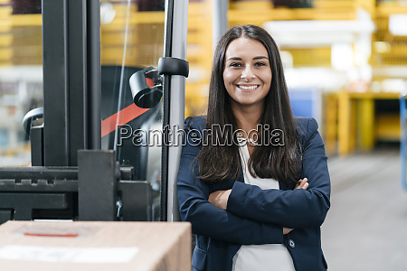 confident woman standing in logistics center