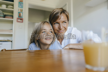 smiling mother and daughter sitting at