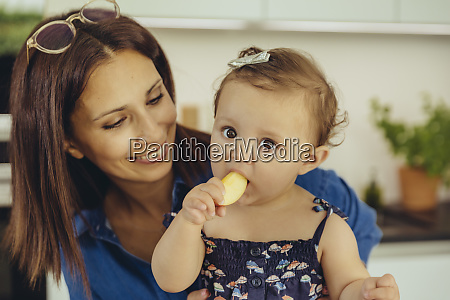 mother watching baby daughter eating an