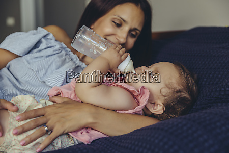 mother watching her baby girl drinking