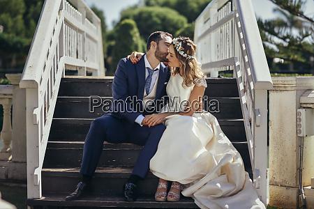 bridal couple sitting on stairs enjoying