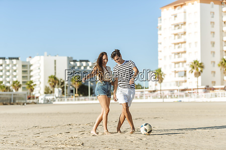 happy young couple playing soccer on