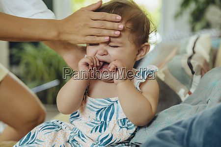 mother taking temperature of her crying