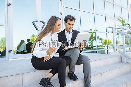 businesswoman and businessman working with tablet