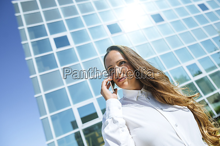 smiling businesswoman on cell phone outside