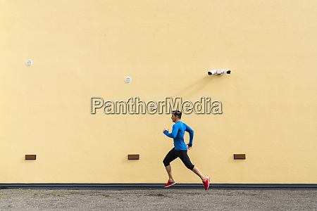 sportive man running along yellow wall