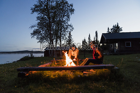 friends sitting at a campfire watching