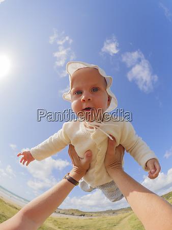 portrait of baby girl holding aloft
