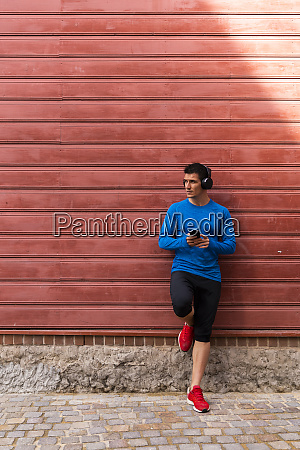 athlete leaning against house wall holding