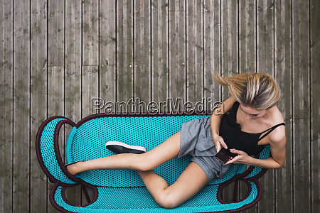 young woman sitting on turquoise couch
