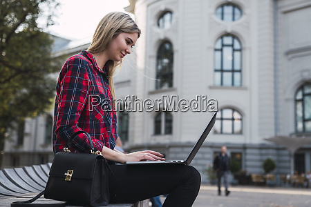 fashionable young woman sitting on bench