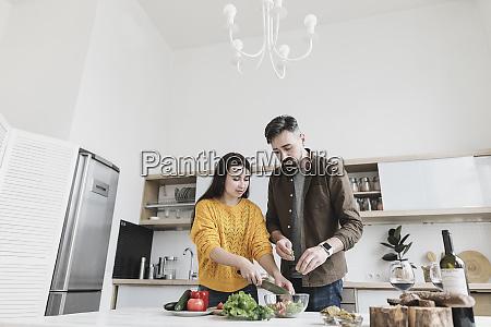 couple preparing salad together in modern